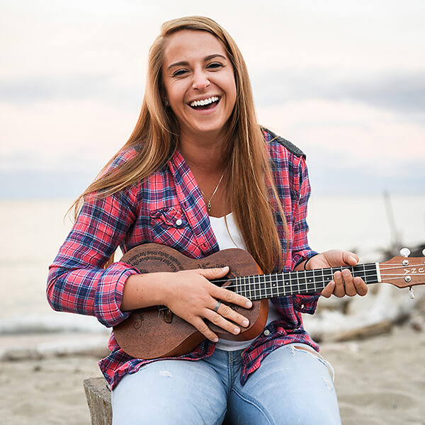 A student plays the ukulele at the beach